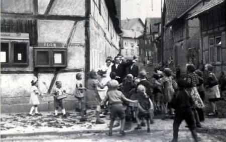 An der Ecke zur Kirchgasse wird das Brautpaar gehemmt. Der Bräutigam wirft Kleingeld unter die Kinder, damit sie den Weg freigeben.
