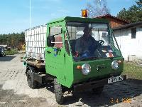 Grünes Multicar mit Bewässerungsbehälter