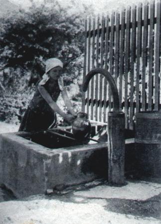 ein kind holt mit einem Krug Wasser am Brunnen